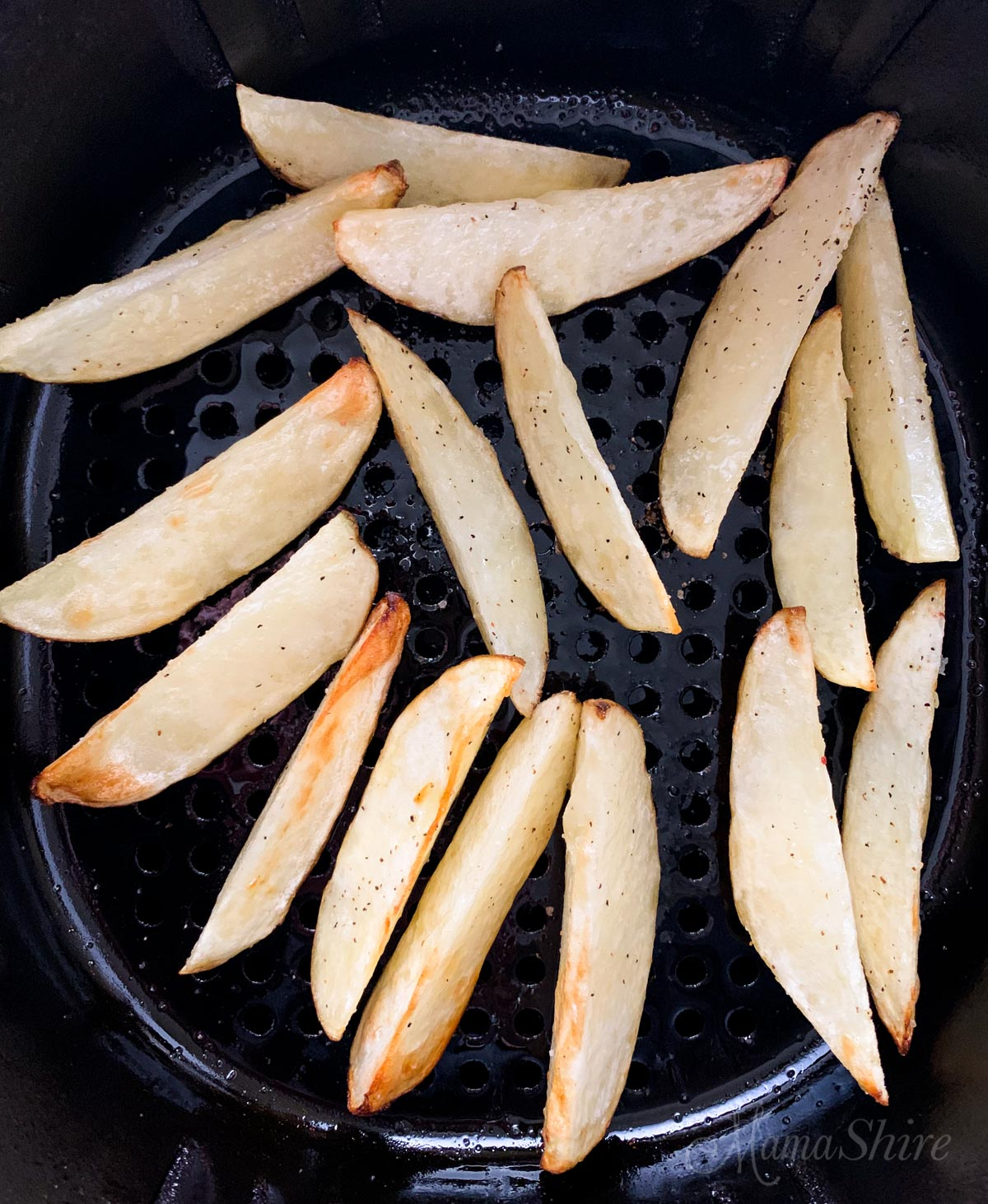 Potato wedges in the air fryer halfway cooked.