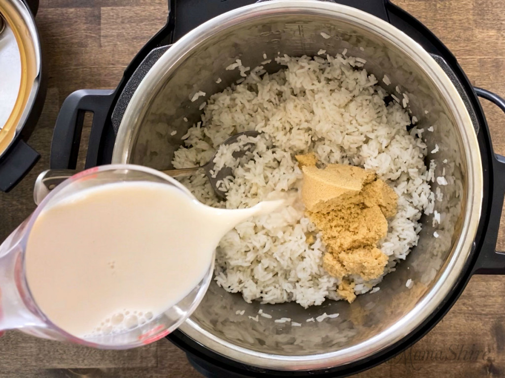 White rice and brown sugar in an Instant Pot with a cup of almond milk pouring on top of it.