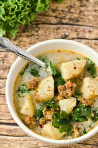 A white bowl with dairy-free soup that has potatoes, kale, and sausage.