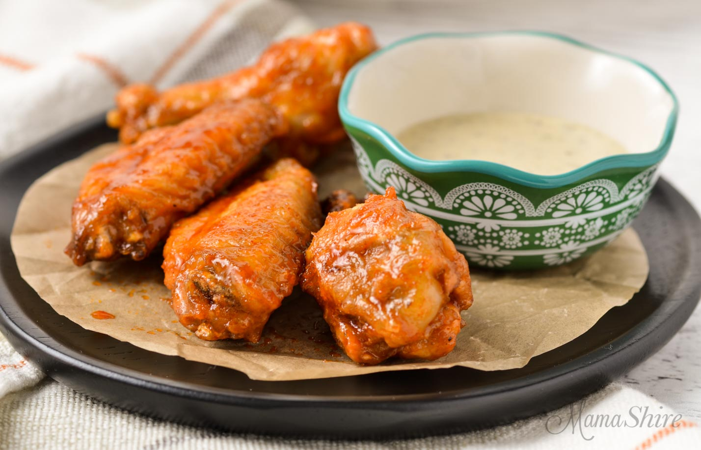 A plate of Korean chicken wings with a small bowl of ranch dressing.