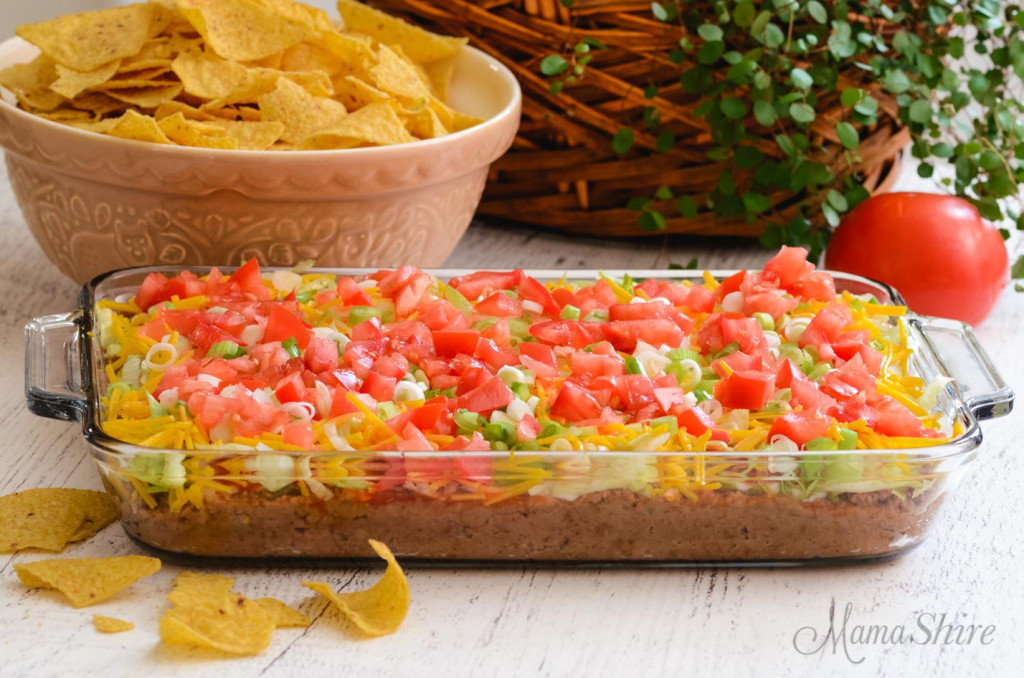 A full glass casserole dish with dairy-free layered bean dip in it with a bowl of tortilla chips behind it.