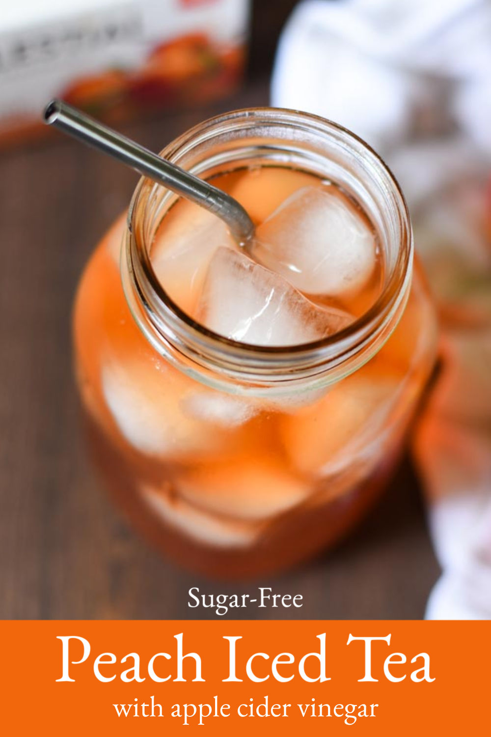 A quart jar filled with ice and peach tea.