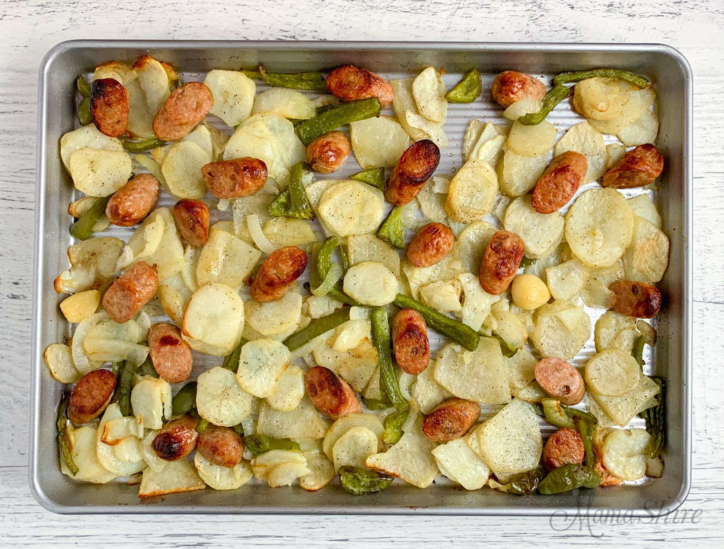 Sheet pan with roasted chicken sausage and potatoes.