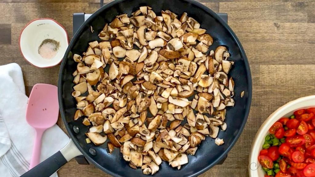 A skillet full of chopped mushrooms.