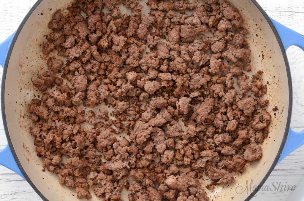 One pound ground beef browned and chopped up in a large skillet.