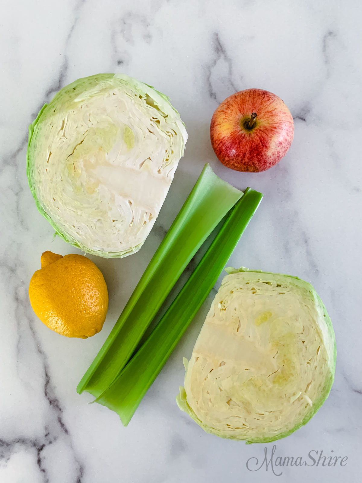 Pictured are some of the ingredients used in this coleslaw, they are cabbage, celery, apple, lemon juice.