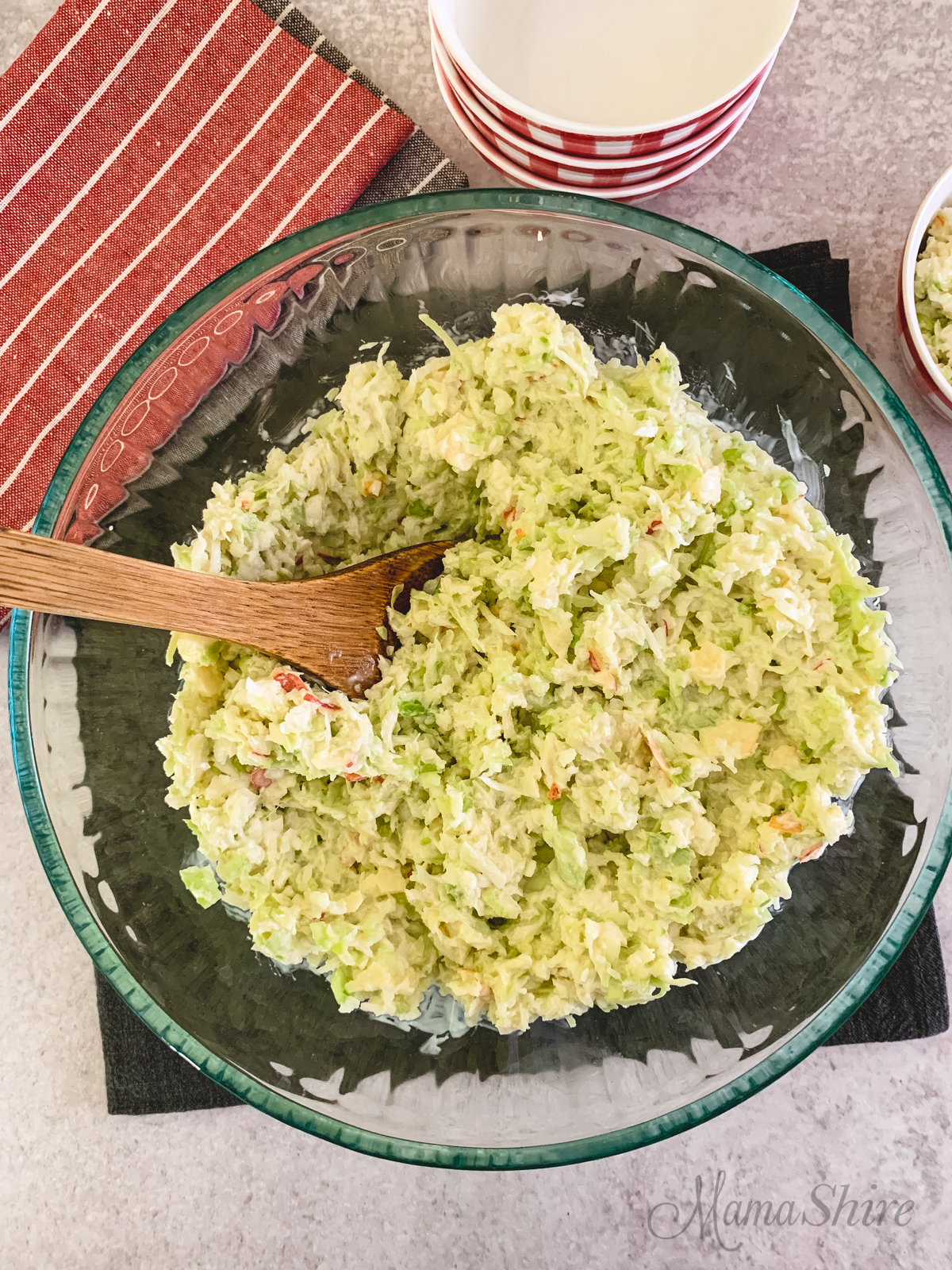 Sweet Apple Coleslaw in a serving bowl with a wooden spoon.