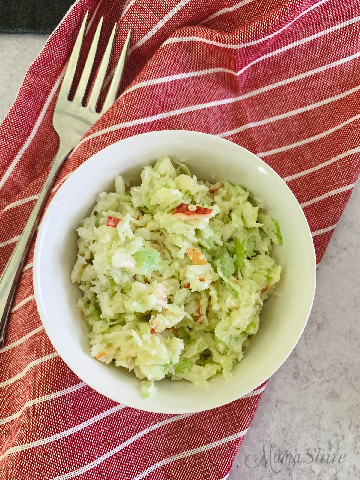 A single serving of sweet coleslaw with a linen red napkin.